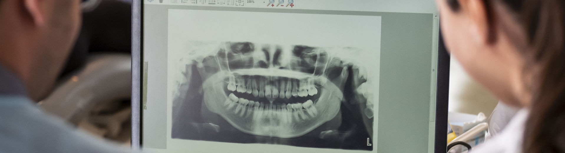 Two dentistry students review an x-ray of teeth and gums.