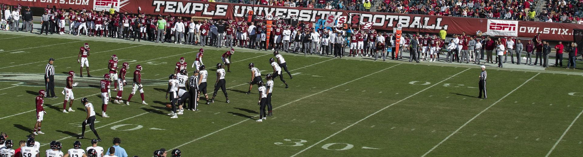 Temple University football players play a game while fans watch from the stands