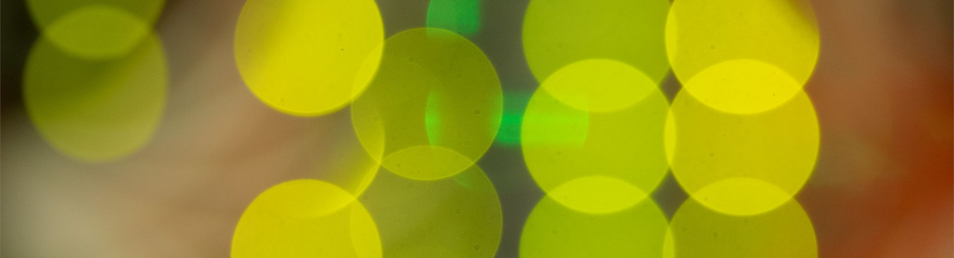 Image is a super close up shot of lights in the back of computer servers resulting in an image of overlapping bright yellow discs of color.