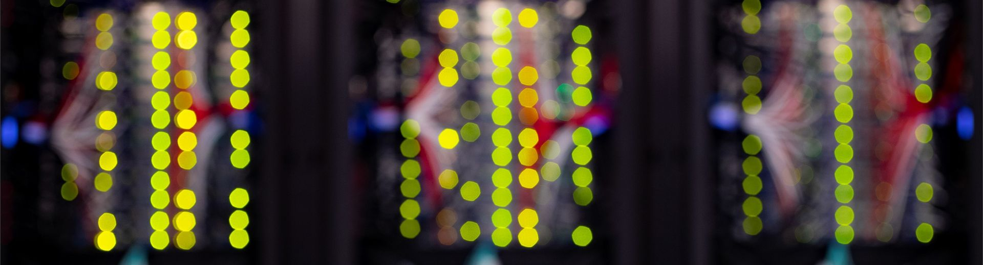 Blurred image of the back of computer servers resulting in a very primary colorscape with columns of bright yellow circles.