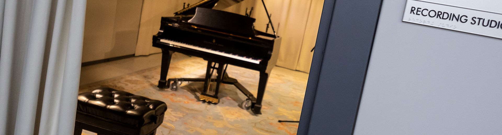 Practice room in music school with a grand piano and blue patterned carpet