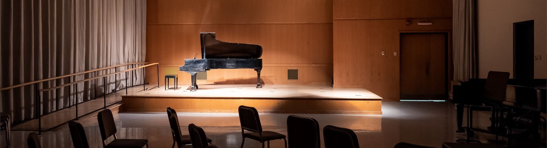 A piano sits on a stage with low lighting.