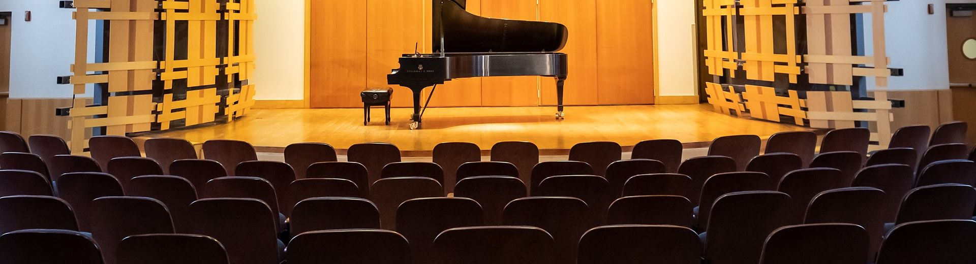 An unattended piano on a stage in an empty auditorium.