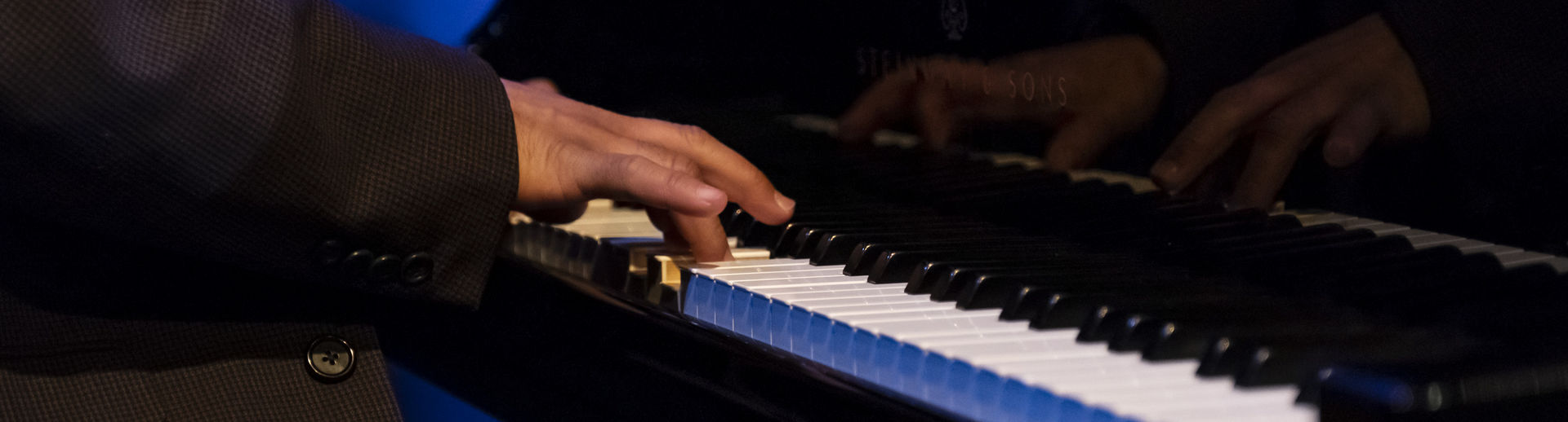 Hands are seen playing the piano.