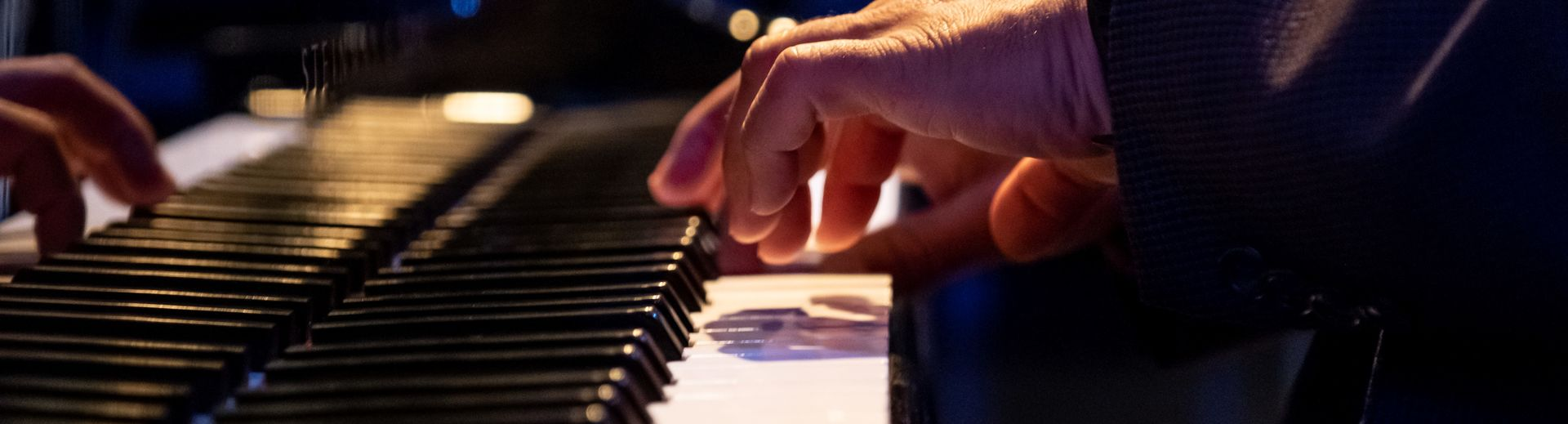 Hands of a pianist on a Steinway grand piano at a performance