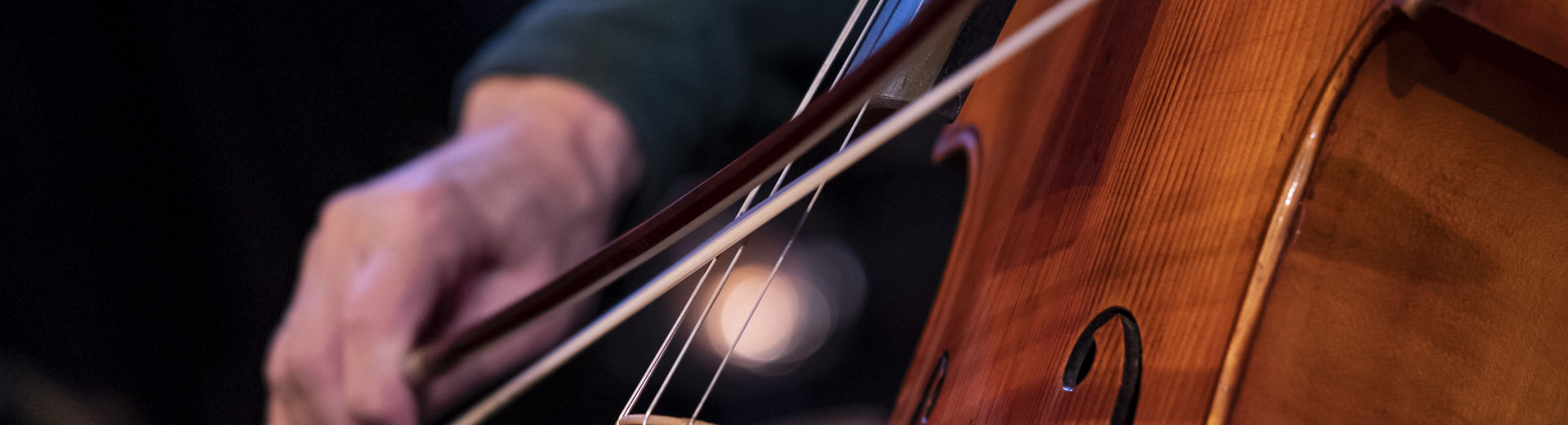 Close up image of a student playing the cello in a performance.