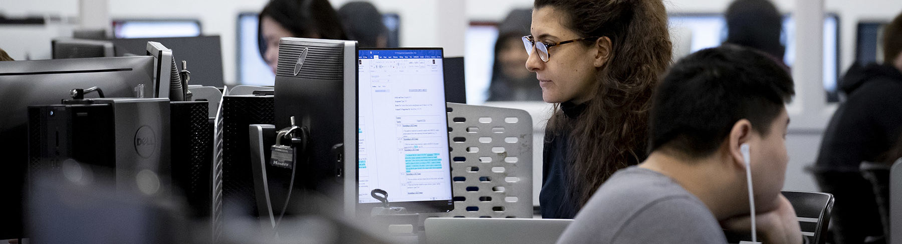 A woman sitting and looking at a computer screen in a technology lab.