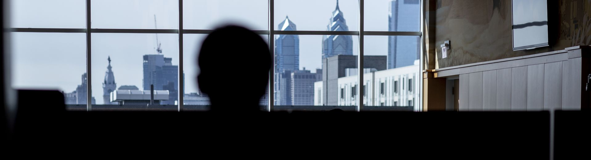 A student looks at the Philadelphia skyline through the windows of a building at Temple University.