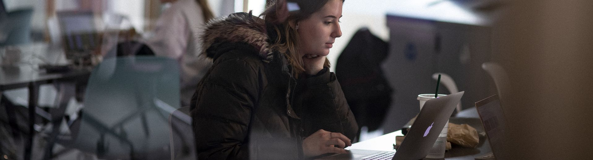 A girl sitting in front a computer doing school work.