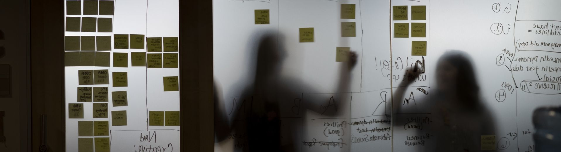 Students attach post-it notes to a glass surface, working on a project.