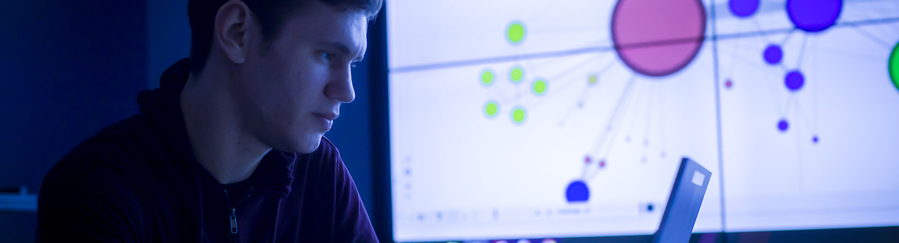 A student looks at his computer with digital data projected on a screen behind him.