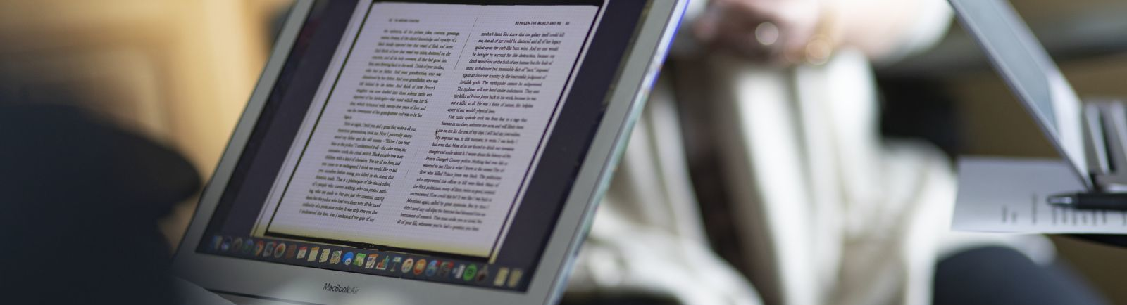 Laptops with screens full of text documents are seen in a classroom setting.