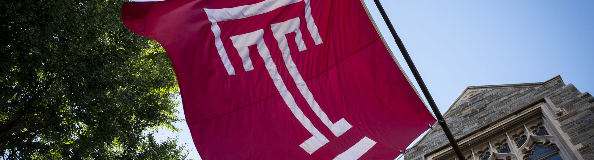 The Temple cherry T flag waves in front of a blue sky on a sunny day