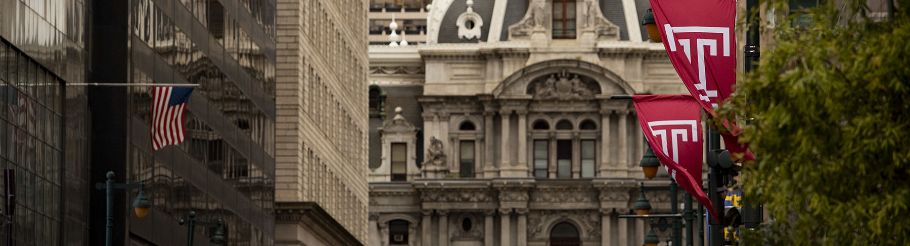 Philadelphia's City Hall building on Market Street lined with cherry red Temple T flags