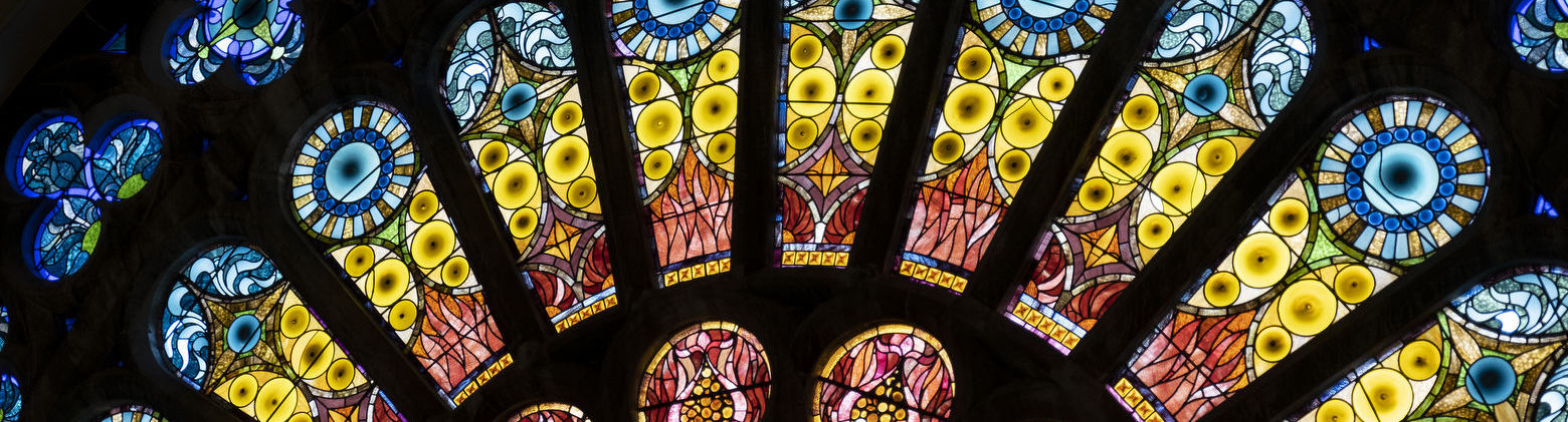 The interior of a stained glass window with blue, green, yellow and red glass.