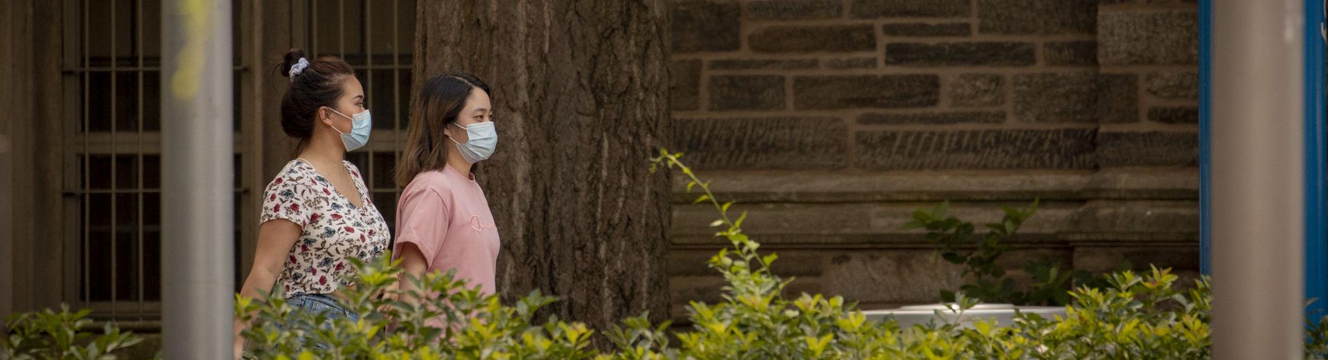 Two Temple staff members wearing masks walk across campus