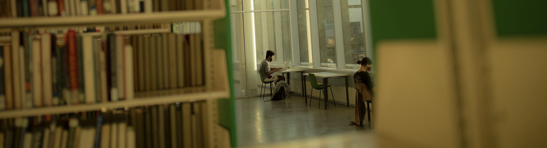 Socially distanced students studying at desks in library