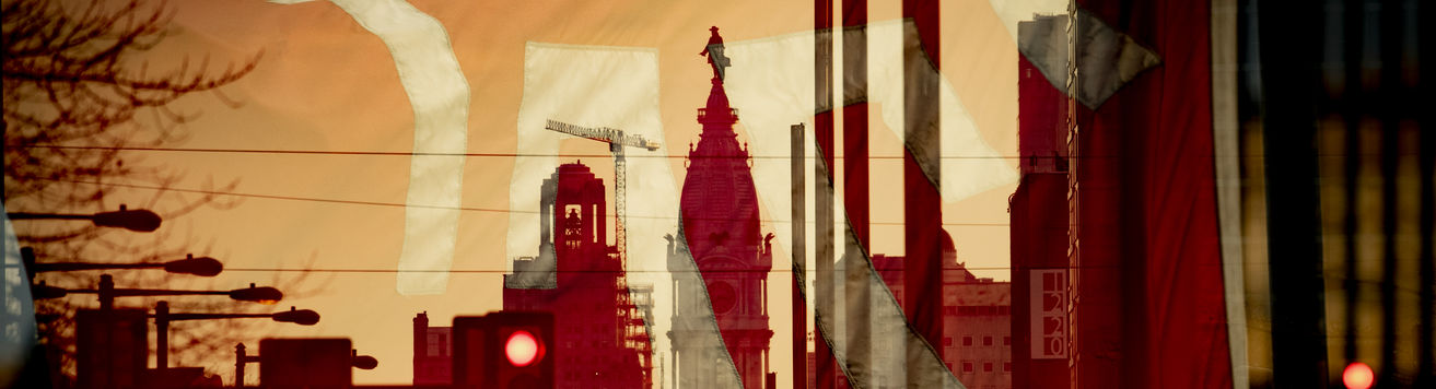 A Temple flag superimposed over an image looking south on Broad Street with City Hall in the center.