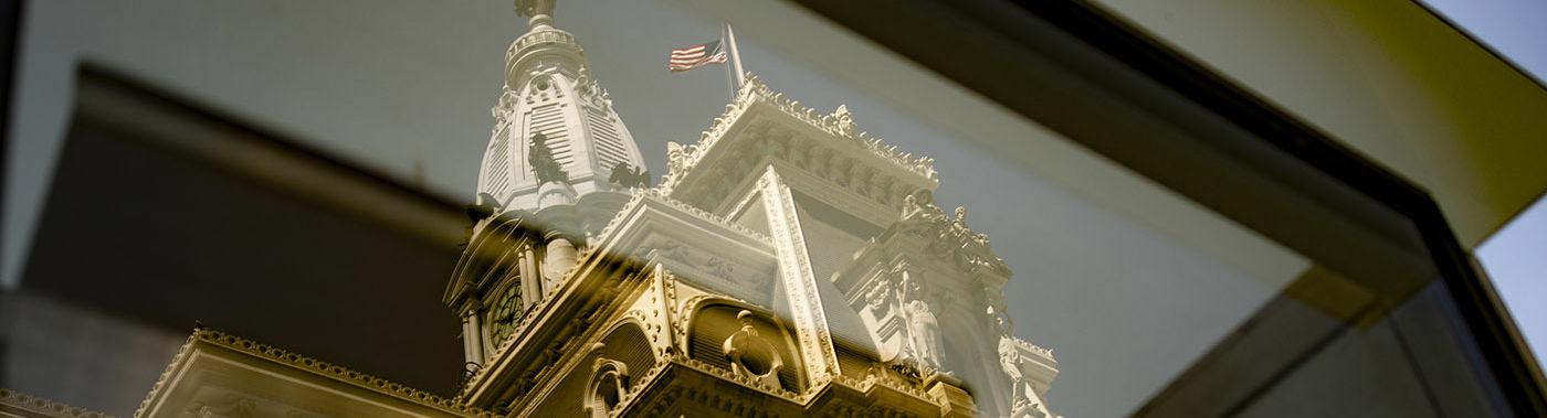 Philadelphia City Hall is seen through a window.