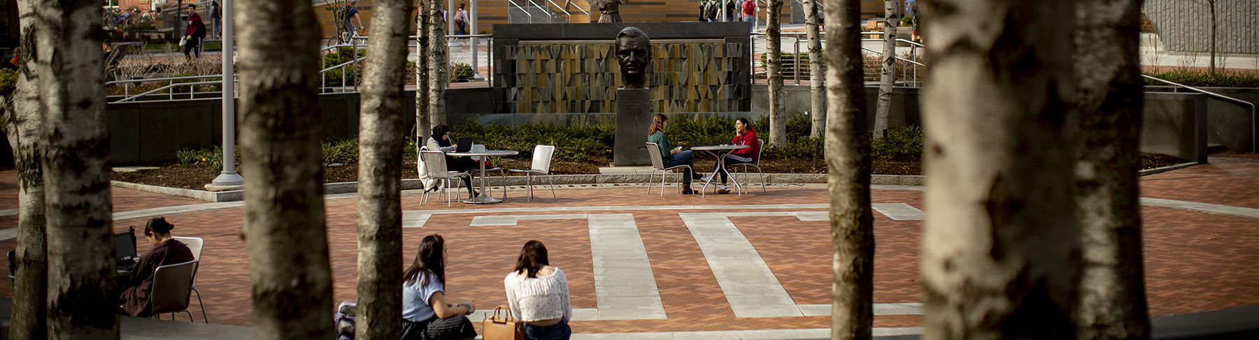 Students sitting in O Conner Plaza on a clear fall day