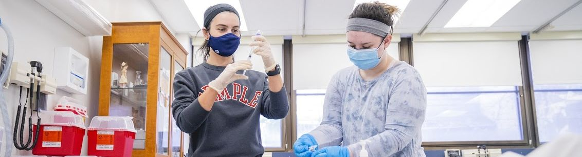 A pair of Temple student nurses working in a faux professional setting.