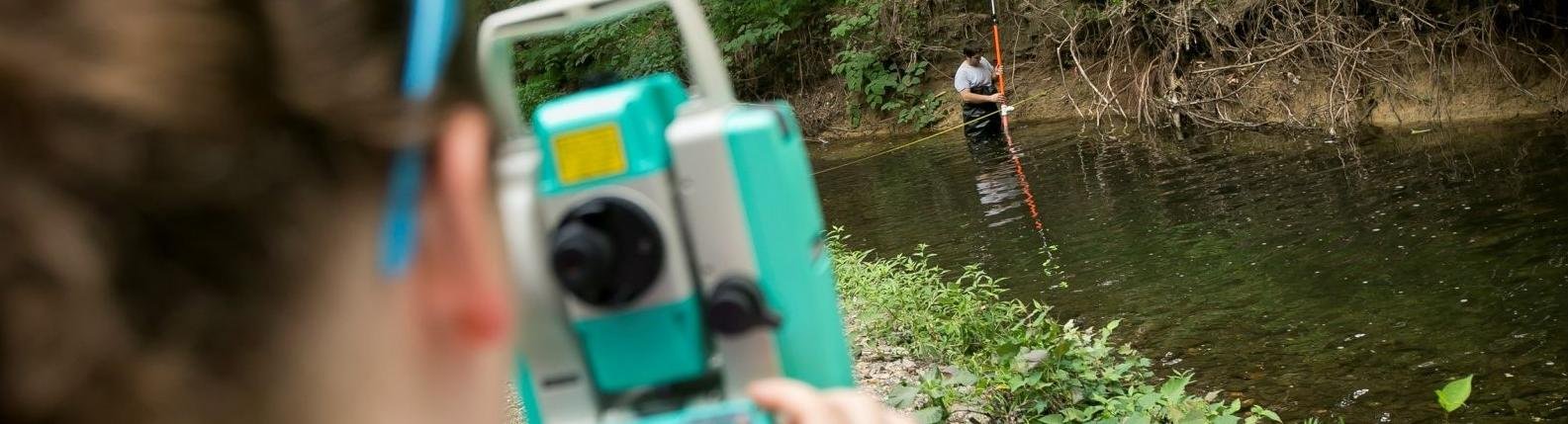 Two Temple students survey a local creek.