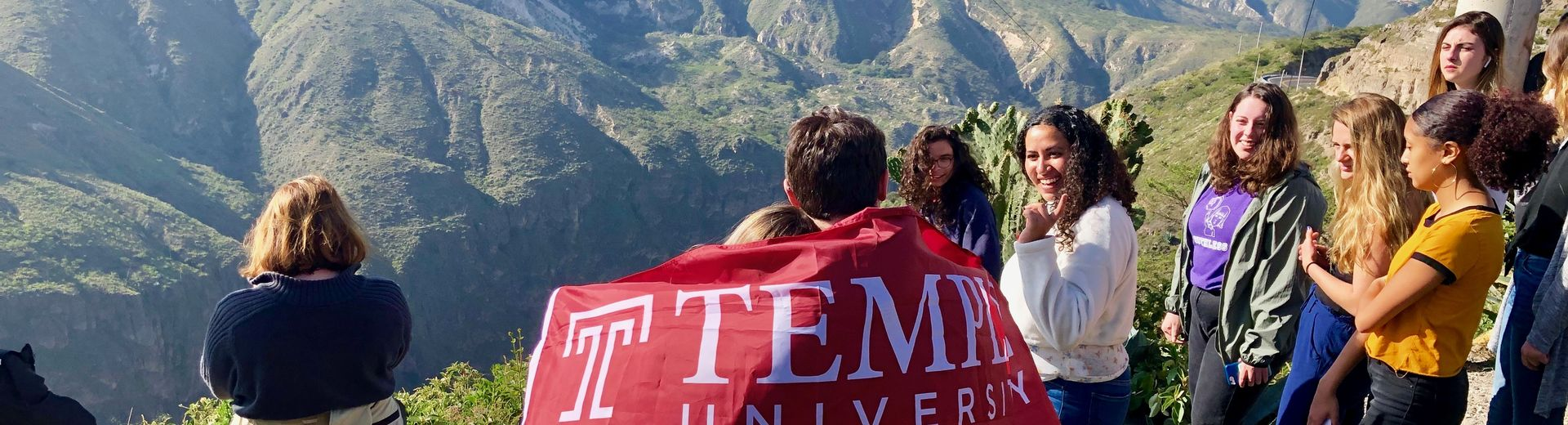Students on top of a mountain carrying a cherry red Temple flag