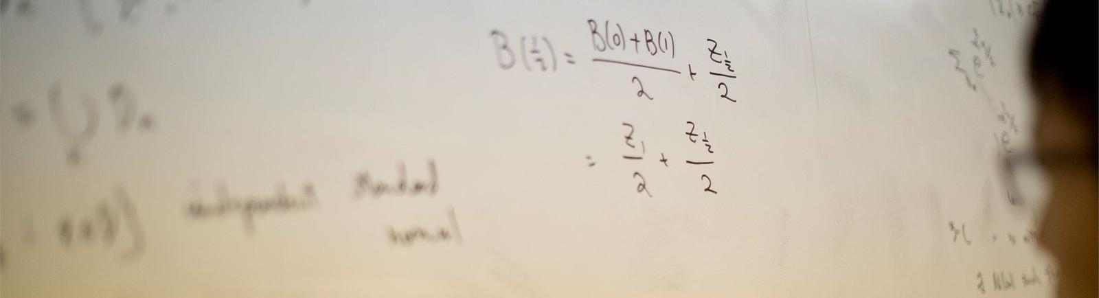 Student writing math equation on white board in a College of Science and Technology classroom.