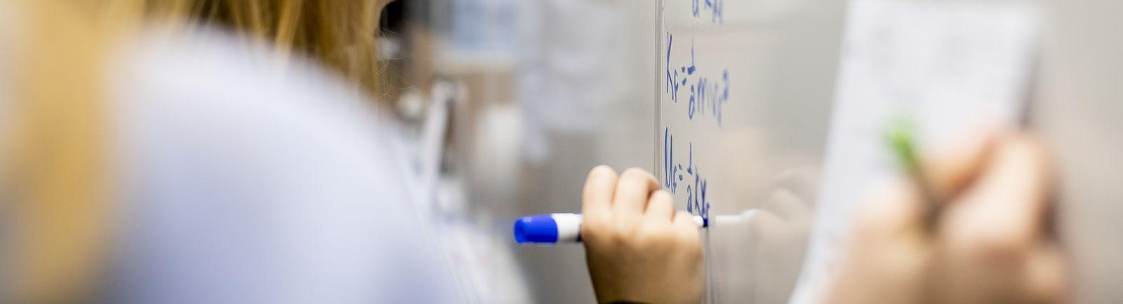 Temple students maps out complex problems on white board