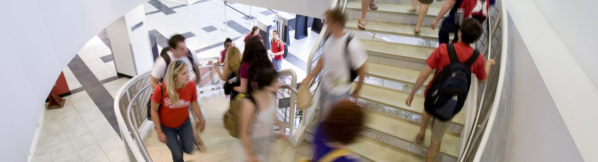 students walking to class up a spiral staircase