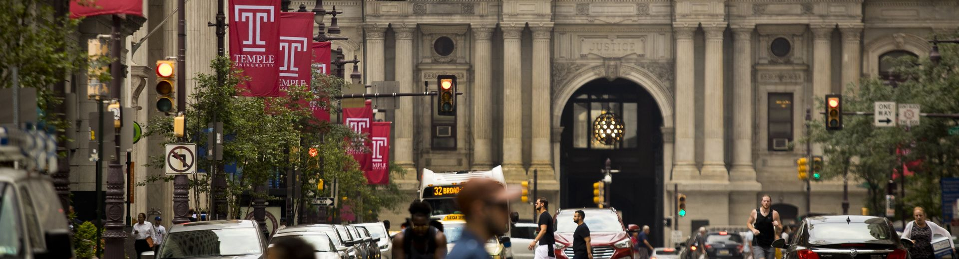 Temple University banners hang from street lamps, with Philadelphia's City Hall in the background.