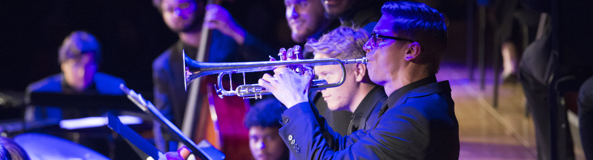 Student playing the trumpet at a live performance.