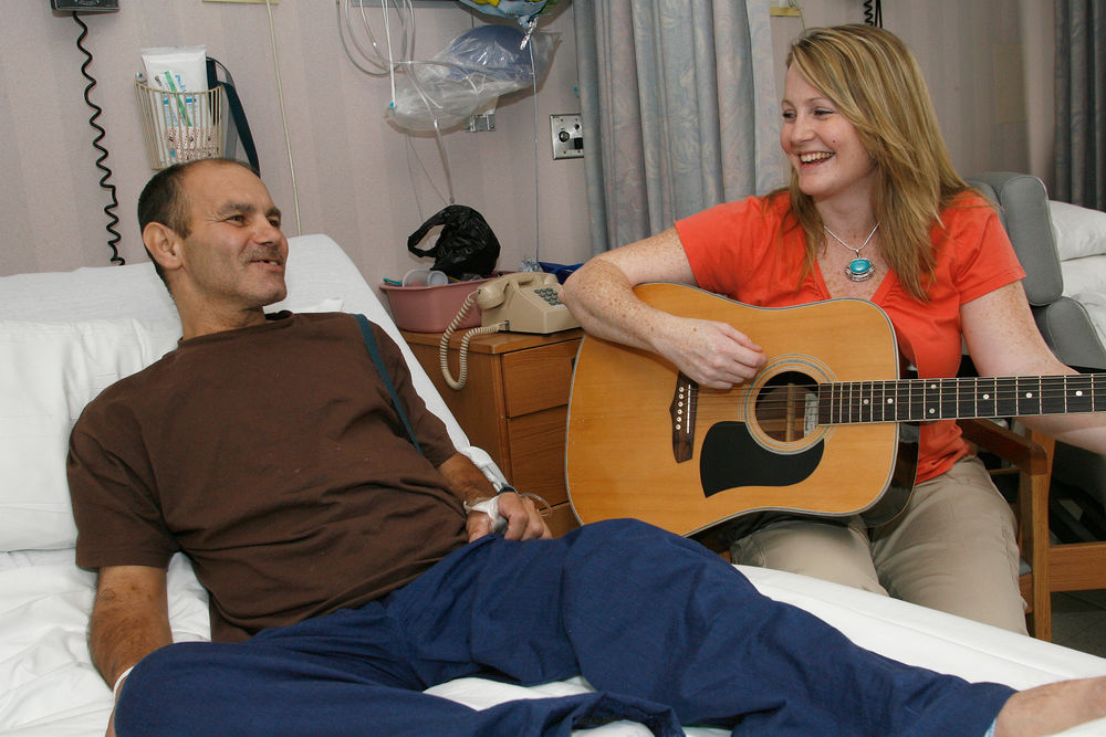 A music therapist plays guitar for a hospital patient.