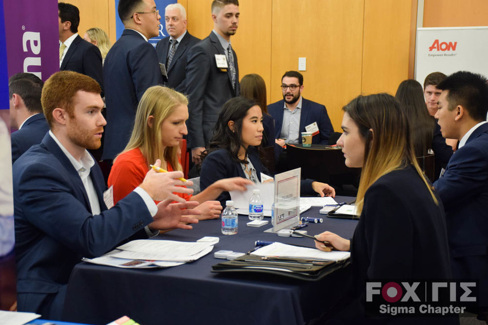 Students in suits having a discussion at a meeting.