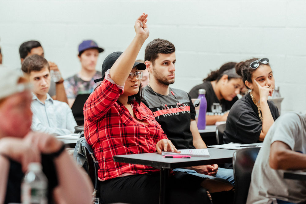 A College of Liberal Arts student raises her hand to ask a question in class.