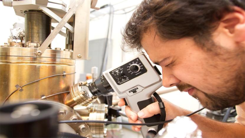 A male physics student using an instrument to conduct research in a lab.
