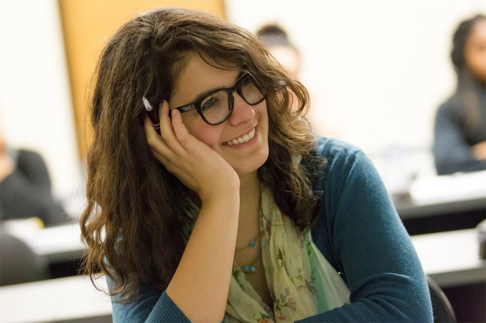 A bespectacled student, her face resting in her left hand, smiles during a class lecture.