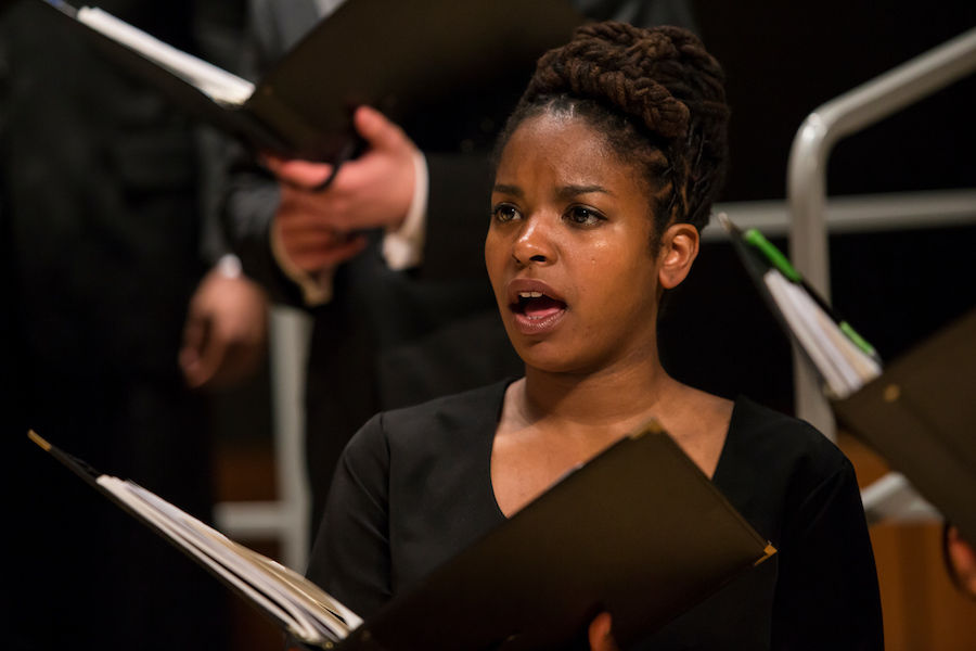 Choir singer holding musical score performing in a concert wearing black top