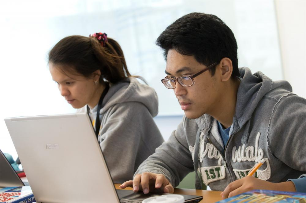Two students work side by side on computers in a Temple classroom.