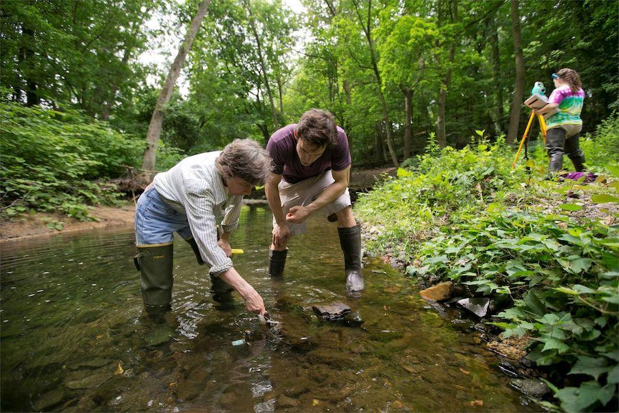 Two environmental science students wearing waders and standing in a stream to test water.
