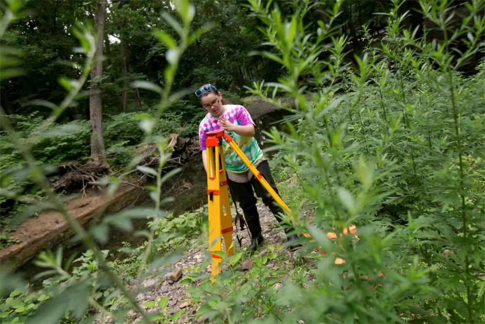 Temple student outside next to a riverbed using land surveying equipment.