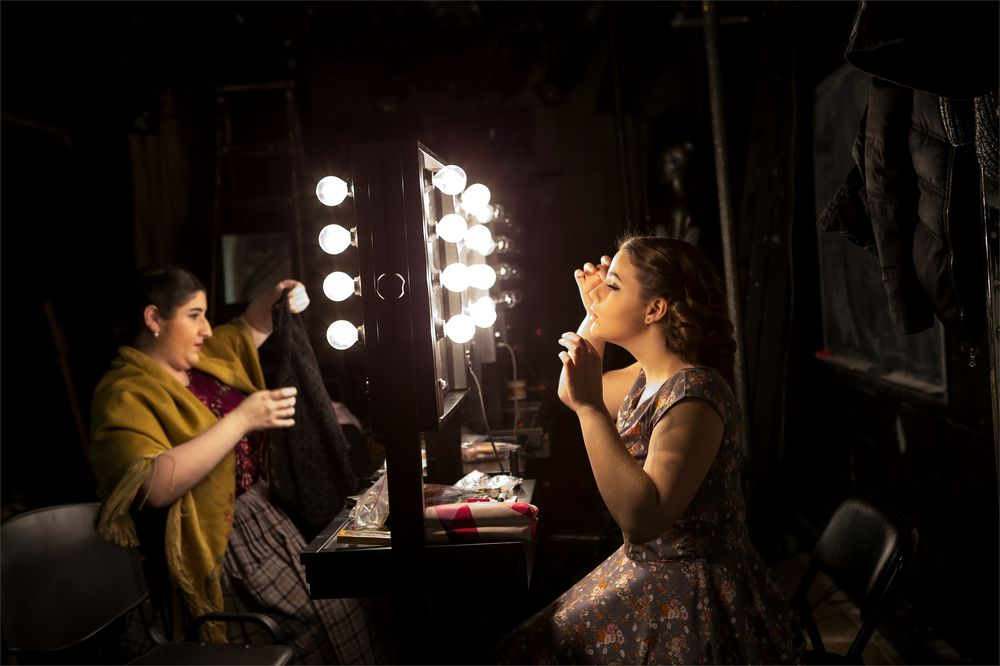 Two female students apply makeup backstage before a show.