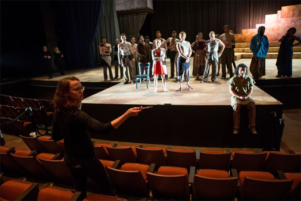 A female student is directing actors on stage.