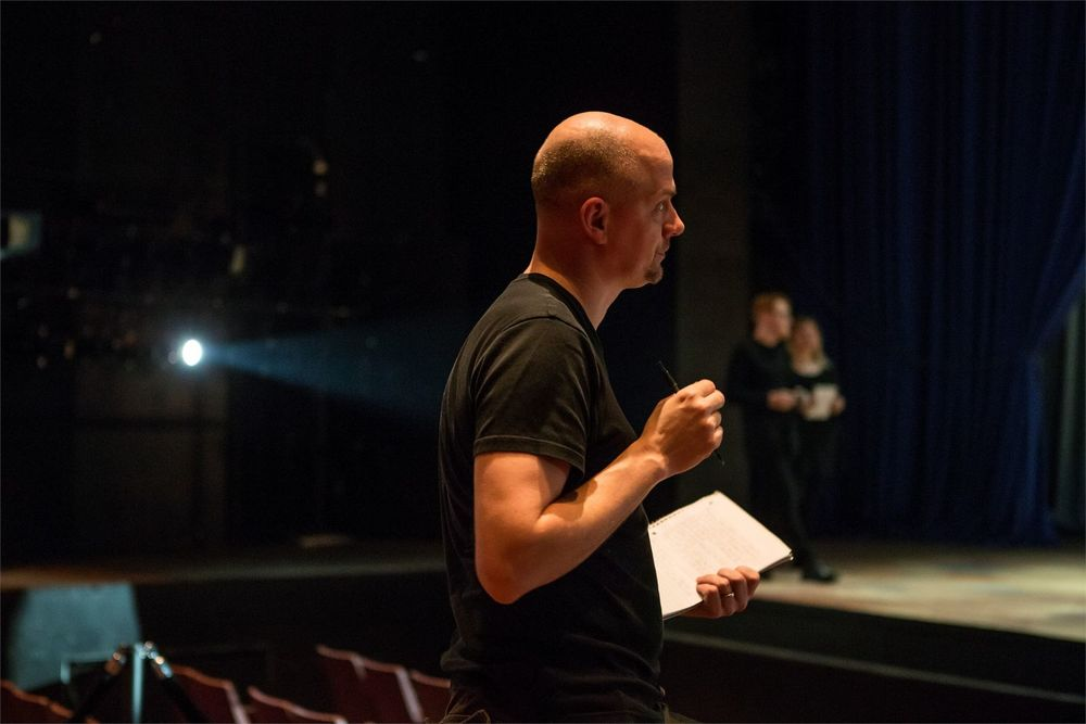 A man holding a pen and notebook looking at activity on stage.
