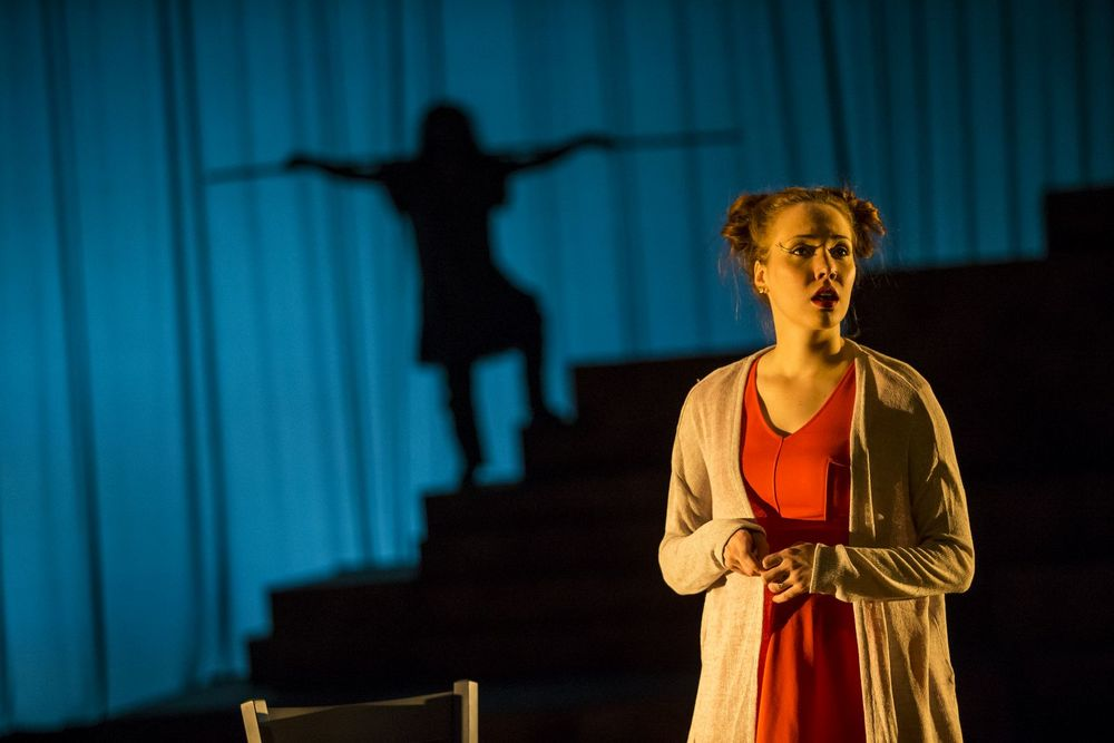 Women stands on stage with a shadow of a man behind her.