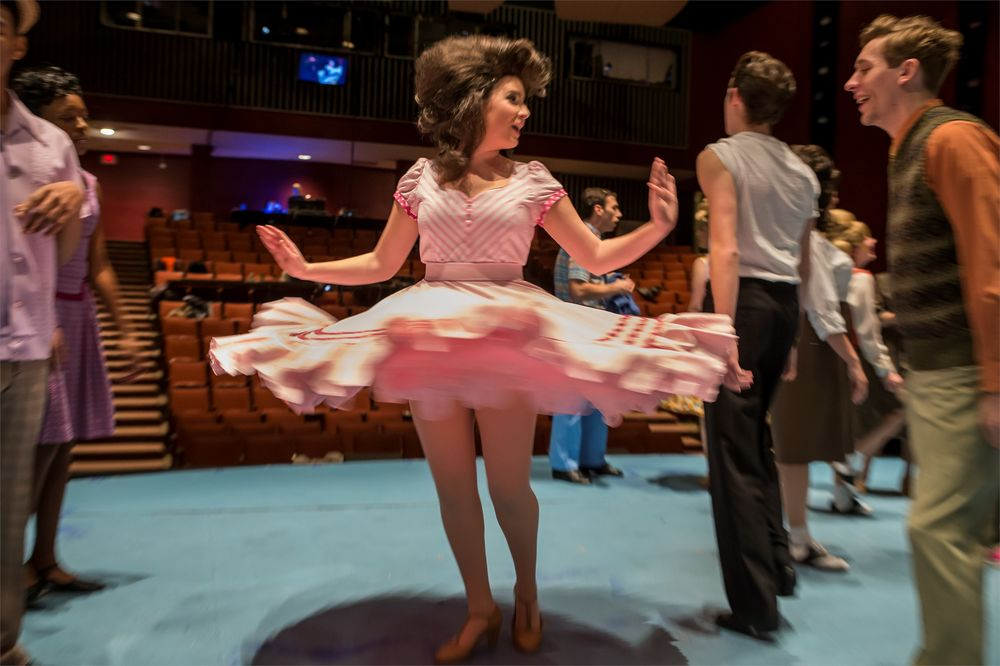 Actor twirling her dress on stage