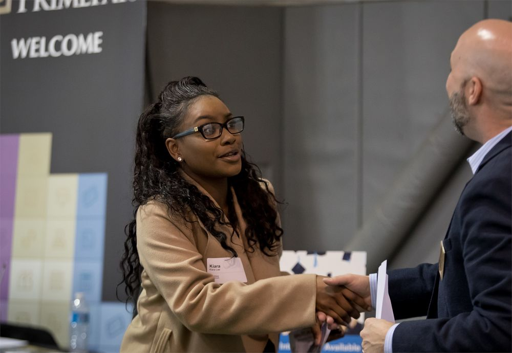 A Temple student shakes hands with a man wearing a suit at a university career fair.