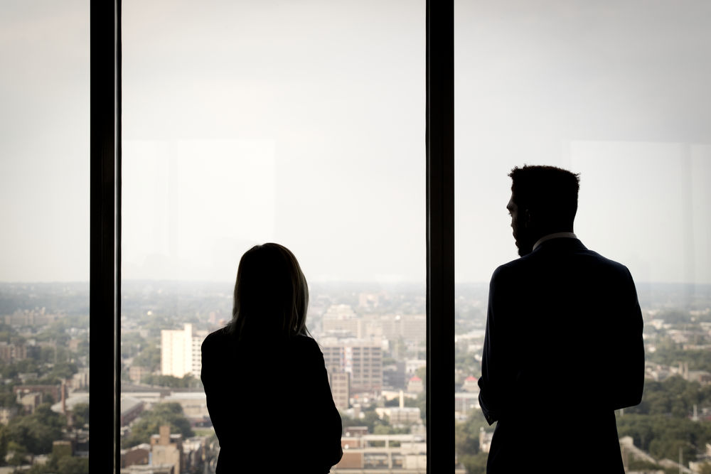 Two students are standing silhouetted against massive windows and looking out onto an expanse of city many floors below.