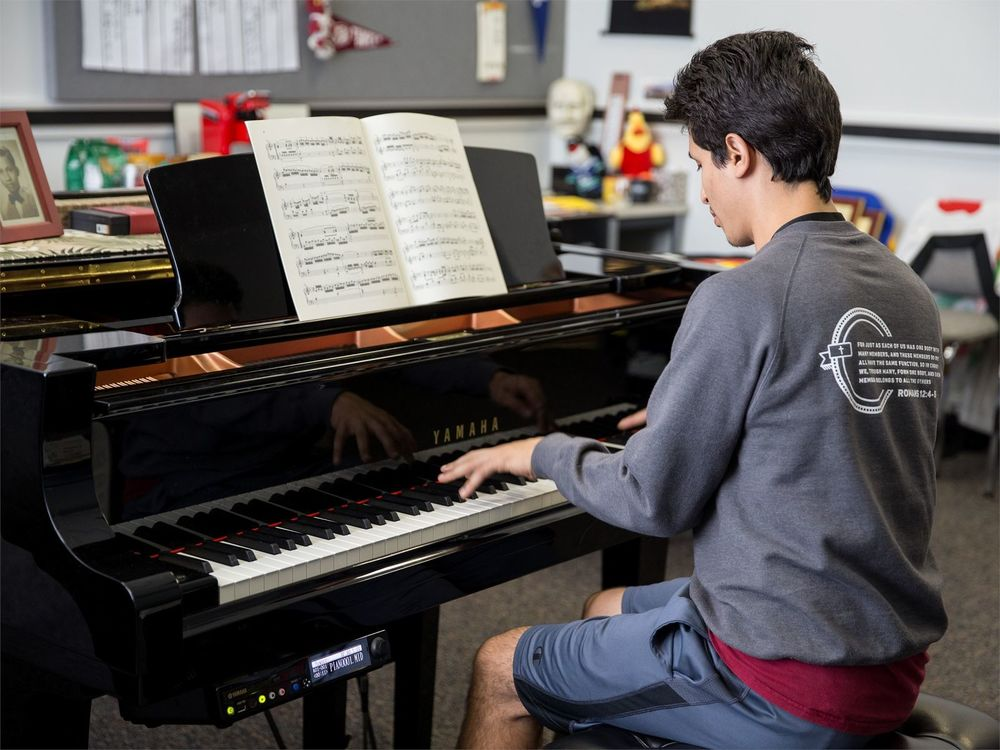 A male student plays a baby grand piano.
