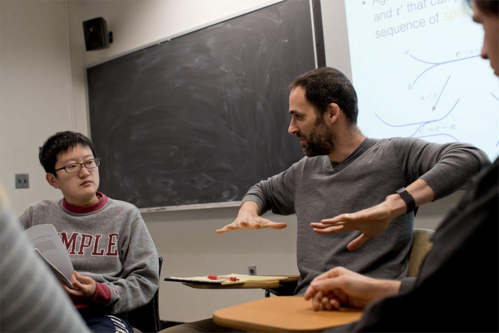 A Temple math professor is talking to his students in a classroom.